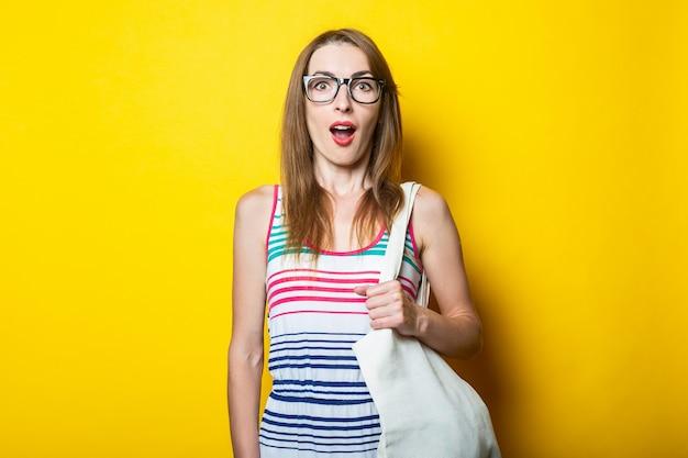 Überraschte junge frau in gestreiftem kleid, brille und mit leinentasche auf gelbem hintergrund.