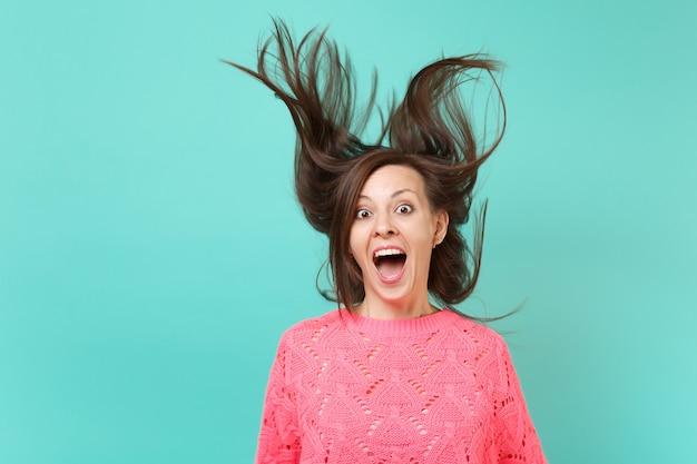 Überraschte junge frau in gestricktem rosa pullover mit flatternden haaren, die den mund weit offen hält und überrascht auf blauem hintergrund aussieht. menschen aufrichtige emotionen, lifestyle-konzept. kopieren sie platz.