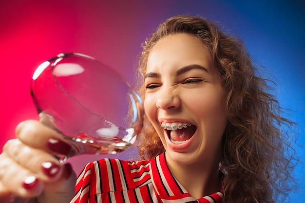 Überraschte junge frau in partykleidung posiert mit glas wein. emotionales weibliches süßes gesicht. blick aus dem glas