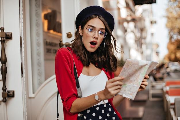 Überraschte junge frau in stilvoller baskenmütze, weißem und rotem outfit, brille, die mit karte auf der terrasse des stadtcafés steht und erstaunt schaut