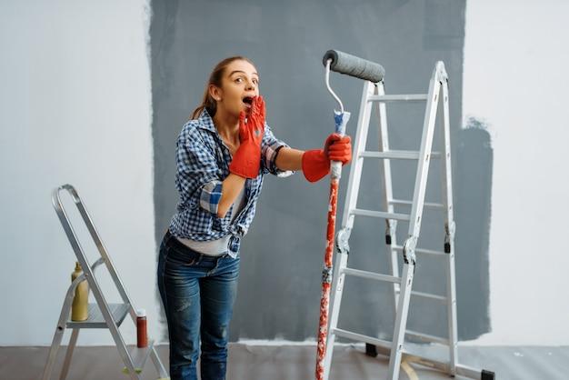 Überraschte junge frau macht hausreparatur, glückliche frau, die wohnungsrenovierung macht, zimmerdekoration renoviert