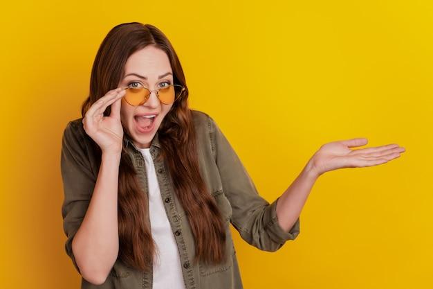 Überraschte junge frau mit brille auf gelbem hintergrund