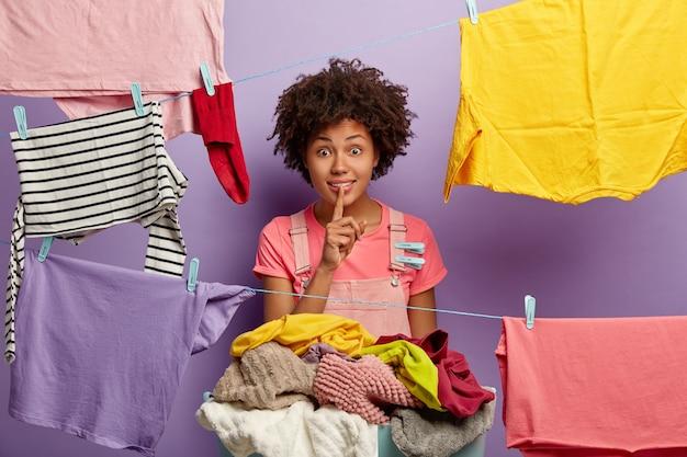 Überraschte junge frau mit einem afro, der mit wäsche im overall aufwirft