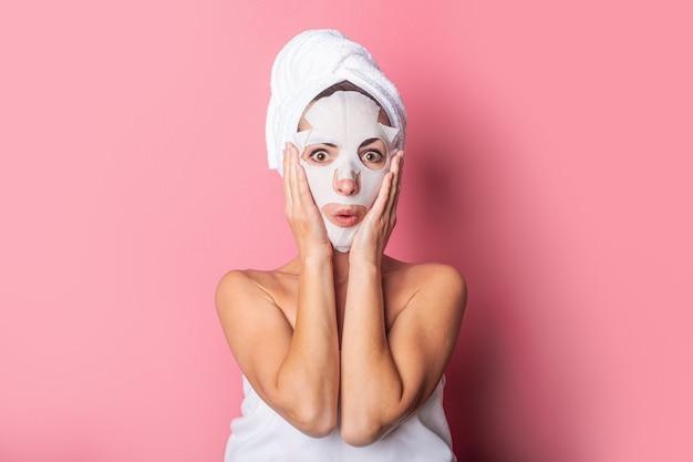 Überraschte junge frau mit einer kosmetischen maske auf ihrem gesicht auf einem rosa hintergrund
