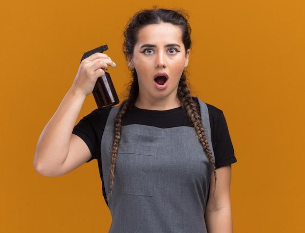 Überraschte junge friseurin in uniform, die sprühflasche lokalisiert auf orange wand hält