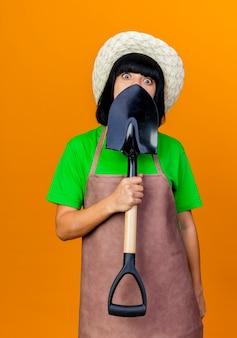 Überraschte junge gärtnerin in uniform mit gartenhut hält und schaut über spaten