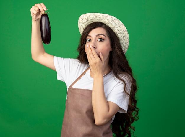 Überraschte junge gärtnerin in uniform mit gartenhut legt hand auf mund und hält aubergine isoliert auf grüner wand mit kopierraum