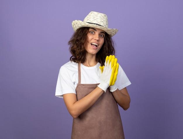 Überraschte junge gärtnerin in uniform mit gartenhut und handschuhen, die gebetsgeste zeigen