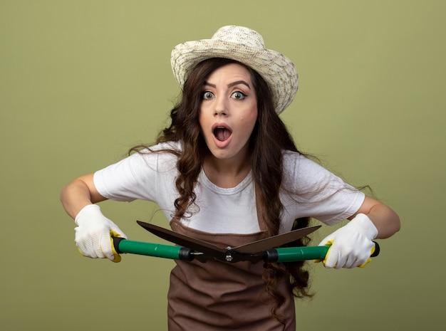Überraschte junge gärtnerin in uniform mit gartenhut und handschuhen hält gartenschere isoliert auf olivgrüner wand