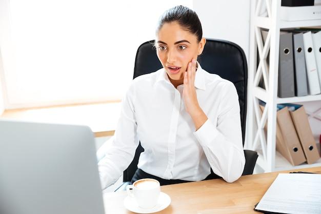 Überraschte junge geschäftsfrau, die auf laptop schaut, während sie im büro sitzt