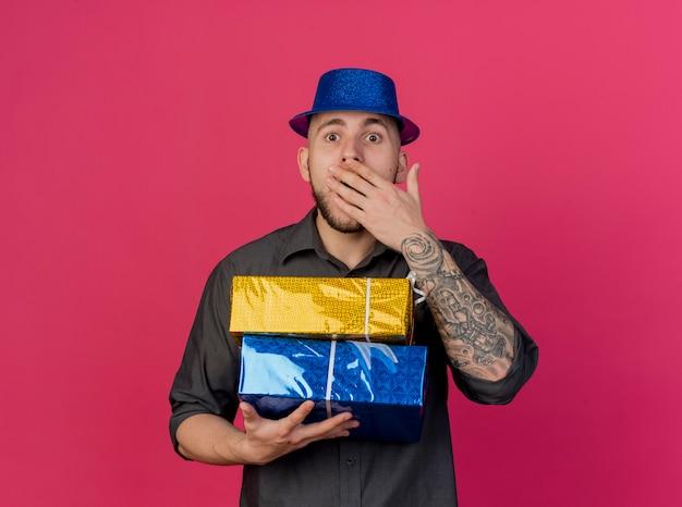 Überraschte junge gutaussehende slawische partei kerl, der partyhut hält, der geschenkverpackungen betrachtet kamera betrachtet, die hand auf mund lokalisiert auf purpurrotem hintergrund mit kopienraum hält