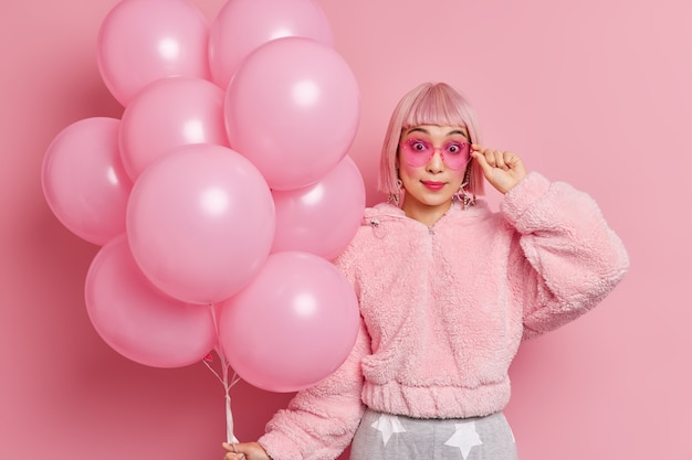 Überraschte junge hübsche asiatische frau mit rosa haaren