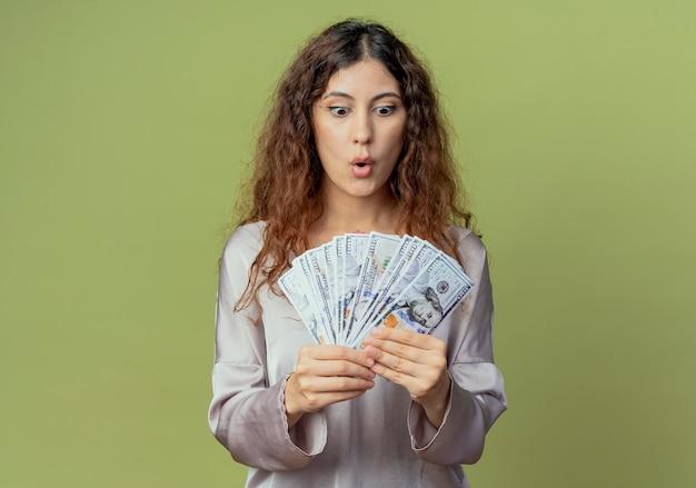 Überraschte junge hübsche büroangestellte, die bargeld hält und betrachtet, das auf olivgrün isoliert wird
