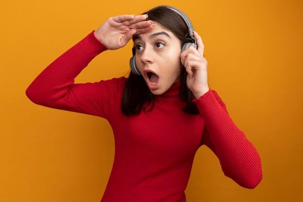 Überraschte junge hübsche kaukasische frau, die kopfhörer trägt und greift, die hand auf der stirn hält und seitlich in die ferne schaut
