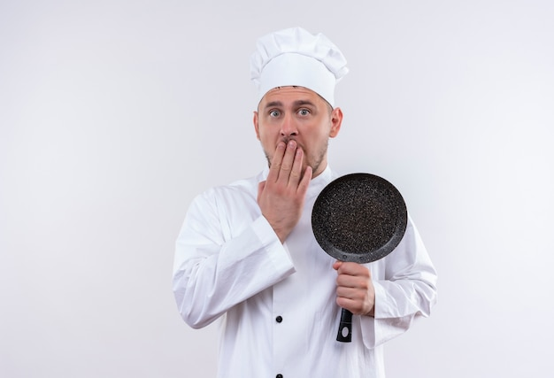 Überraschte junge hübsche köchin in der kochuniform, die bratpfanne hält, die hand auf mund lokalisiert auf weißraum setzt