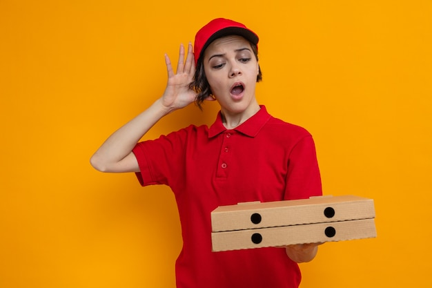Überraschte junge hübsche lieferfrau, die pizzakartons hält und betrachtet