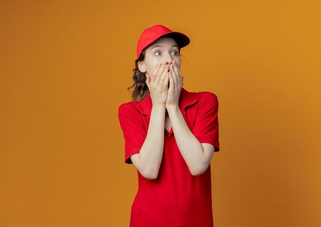 Überraschte junge hübsche lieferfrau in roter uniform und mütze, die seite betrachtet, die hände auf mund setzt