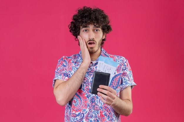 Überraschte junge hübsche lockige reisende mann, die brieftasche und flugtickets mit hand auf wange auf isolierter rosa wand mit kopienraum hält