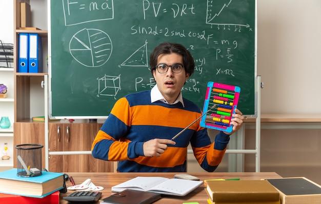 Überraschte junge kaukasische geometrielehrerin mit brille, die am schreibtisch mit schulmaterial im klassenzimmer sitzt und einen abakus zeigt, der mit einem zeigerstock auf die vorderseite zeigt?
