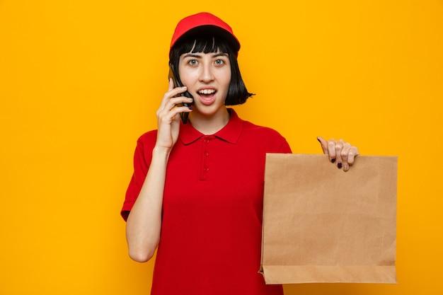 Überraschte junge kaukasische lieferfrau, die papierlebensmittelverpackungen hält und am telefon spricht