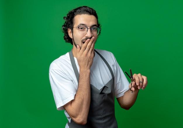 Überraschte junge kaukasische männliche friseur, die brille und welliges haarband in uniform hält, die schere hält und hand auf mund lokalisiert auf grünem hintergrund mit kopienraum setzt