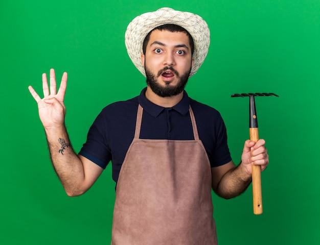 Überraschte junge kaukasische männliche gärtner, die gartenhut hält, der rechen hält und vier mit den fingern lokalisiert auf grüner wand mit kopienraum gestikuliert