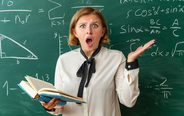 Überraschte junge lehrerin, die vor der tafel steht und ein buch hält, das die hände im klassenzimmer ausbreitet