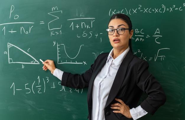 Überraschte junge lehrerin mit brille, die vor der tafel steht, die gestrandet für das brett hält und die hand im klassenzimmer auf die hüfte legt