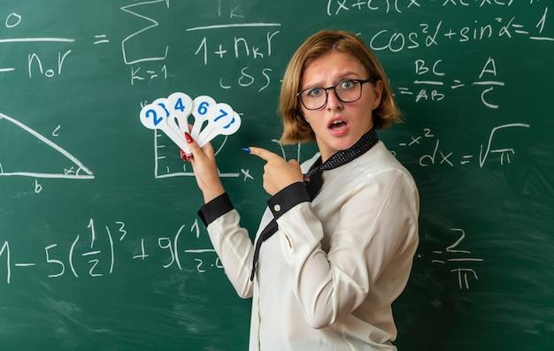 Überraschte junge lehrerin mit brille, die vor der tafel steht und auf nummernfächer im klassenzimmer zeigt