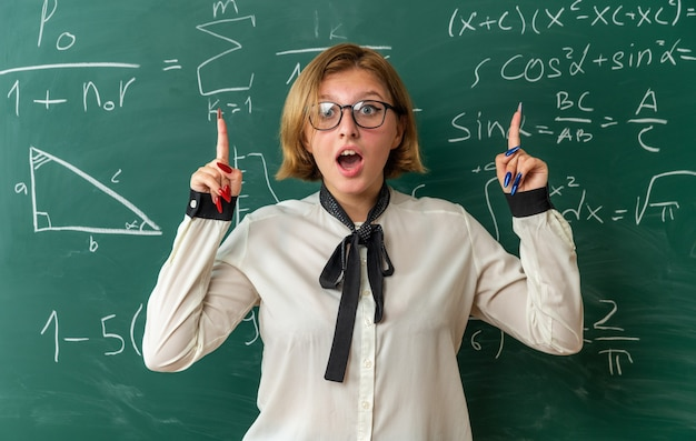 Überraschte junge lehrerin mit brille, die vor der tafel steht, zeigt im klassenzimmer