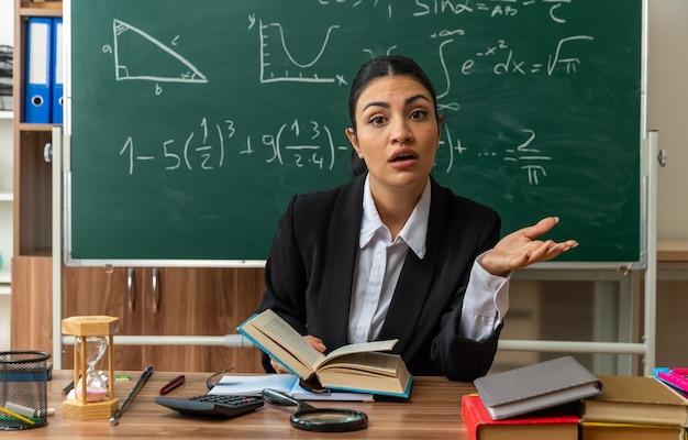 Überraschte junge lehrerin sitzt am tisch mit schulmaterial, das die hand im klassenzimmer ausbreitet