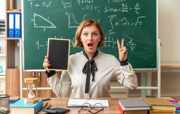 Überraschte junge lehrerin sitzt am tisch mit schulwerkzeugen, die eine mini-tafel halten, die zwei im klassenzimmer zeigt