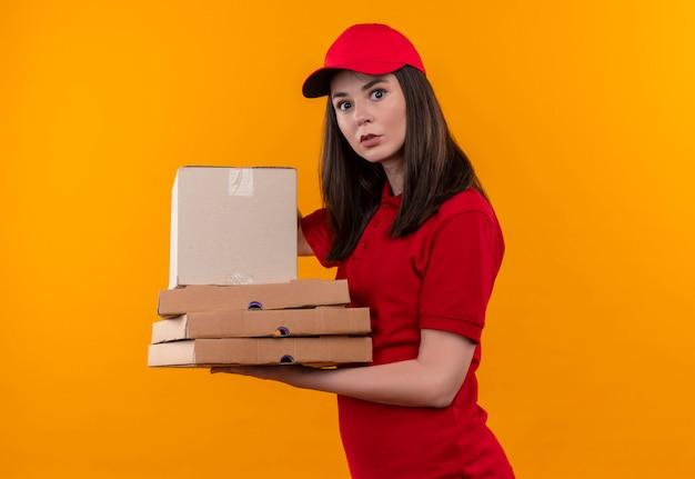 Überraschte junge lieferfrau, die rotes t-shirt in der roten kappe hält, die eine box mit pizzaschachtel auf isolierter gelber wand hält