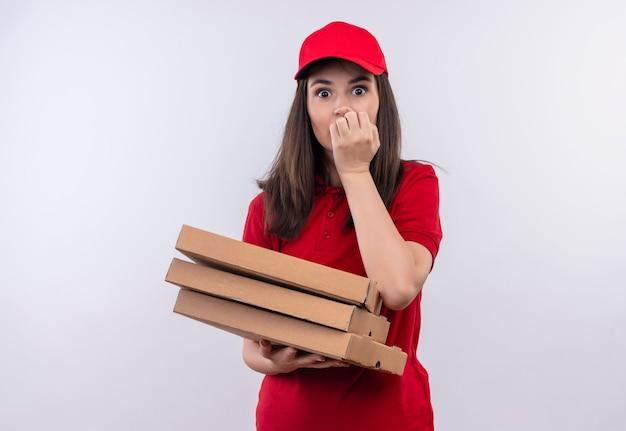 Überraschte junge lieferfrau, die rotes t-shirt in der roten kappe hält, die eine pizzaschachtel auf isolierter weißer wand hält