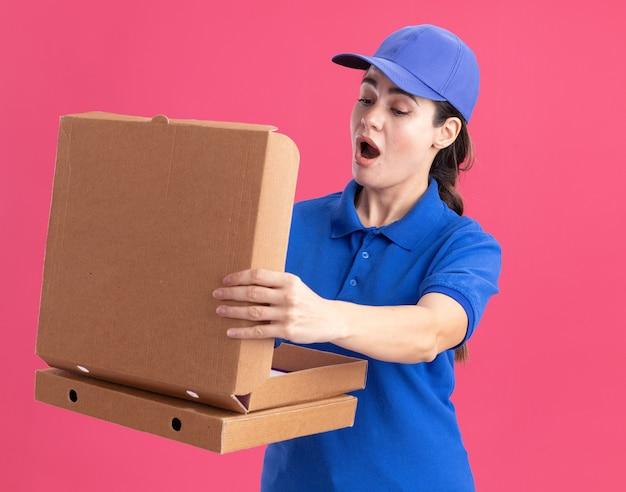 Überraschte junge lieferfrau in uniform und mütze, die pizzapakete hält und eine öffnet, die hineinschaut?