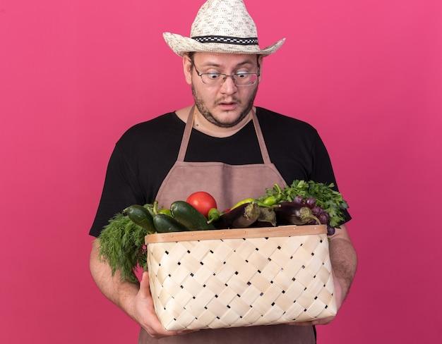 Überraschte junge männliche gärtner tragen gartenhut halten und betrachten gemüsekorb lokalisiert auf rosa wand