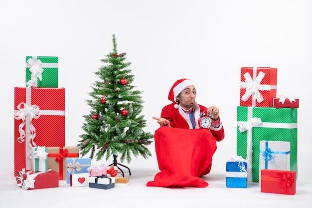 Überraschte junge mann feiern neujahr oder weihnachtsfeiertag sitzen auf dem boden und halten uhr in der nähe von geschenken und geschmücktem weihnachtsbaum