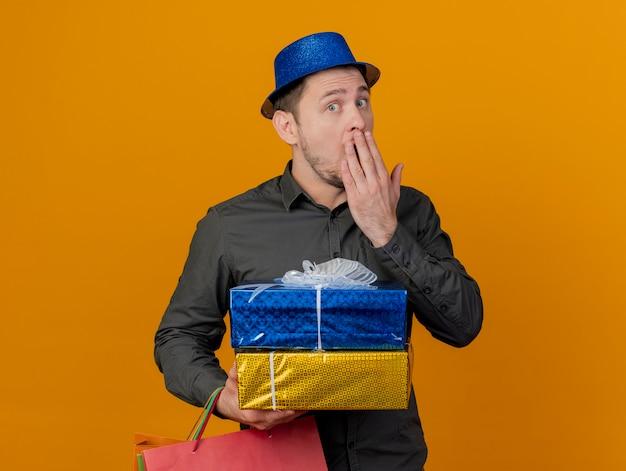 Überraschte junge partei kerl, der blauen hut hält, der geschenkboxen mit tasche und bedecktem mund mit hand lokalisiert auf orange hält