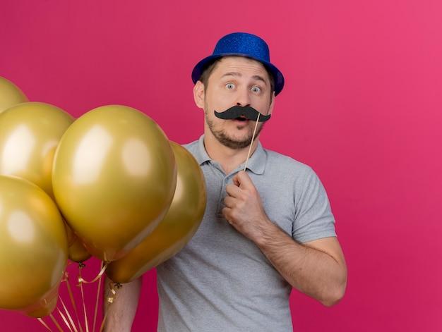 Überraschte junge partei kerl, der blauen hut hält, der luftballons mit falschem schnurrbart auf stock lokalisiert auf rosa hält