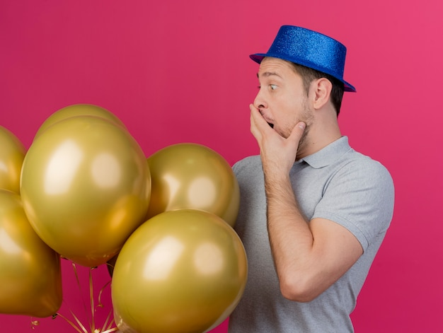 Überraschte junge partei kerl, der blauen hut hält und ballons bedeckt mund mit hand lokalisiert auf rosa hält