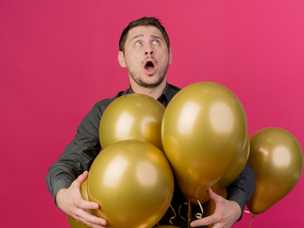 Überraschte junge partei kerl, der schwarzes hemd trägt, das unter luftballons steht, die auf rosa isoliert werden