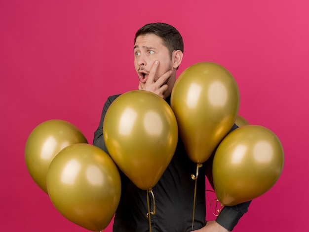 Überraschte junge partei kerl, der schwarzes hemd trägt, das zwischen luftballons steht, packte kinn isoliert auf rosa