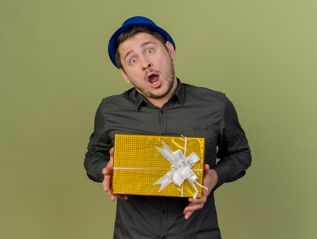 Überraschte junge partei kerl, der schwarzes hemd und blauen hut hält geschenkbox lokalisiert auf olivgrün trägt