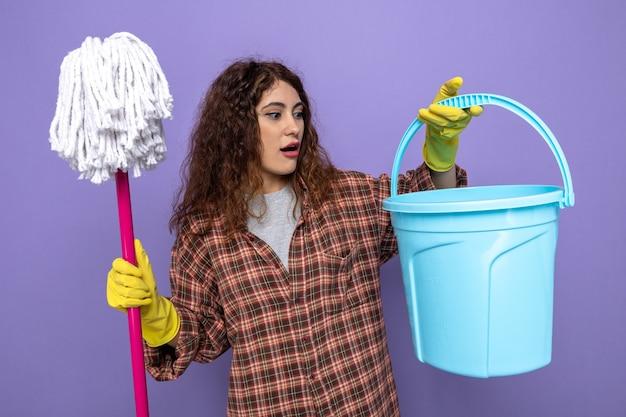 Überraschte junge putzfrau mit handschuhen, die einen mopp mit blick auf den eimer in der hand hält