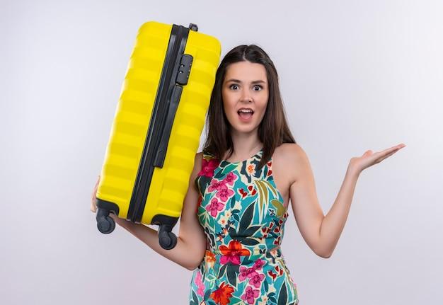 Überraschte junge reisende frau, die mehrfarbiges kleid trägt, hob ihre reisetasche an der weißen wand