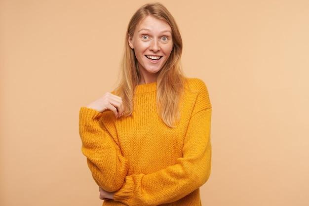 Überraschte junge rothaarige frau mit lässiger frisur, die ihr haar berührt und emotional schaut und auf beige im senfpullover posiert