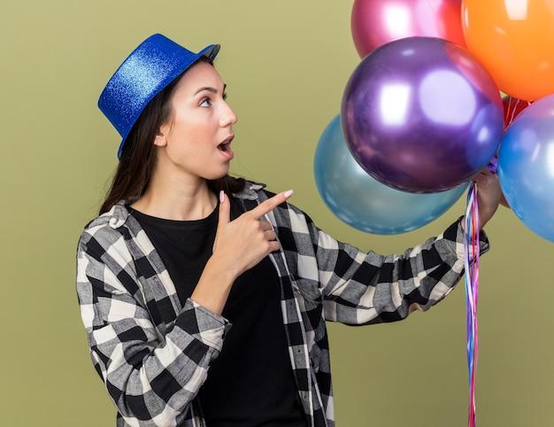 Überraschte junge schöne frau mit blauem hut hält und zeigt auf ballons isoliert auf olivgrüner wand