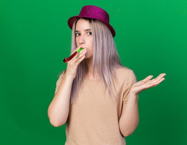 Überraschte junge schöne frau mit partyhut bläst partypfeife, die hand isoliert auf grüner wand ausbreitet