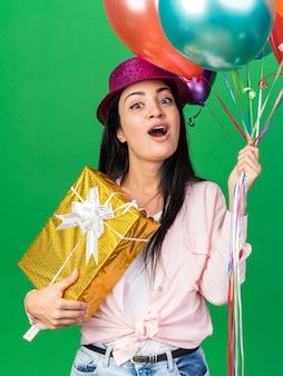 Überraschte junge schöne frau mit partyhut, die luftballons hält, die geschenkbox isoliert auf grüner wand halten