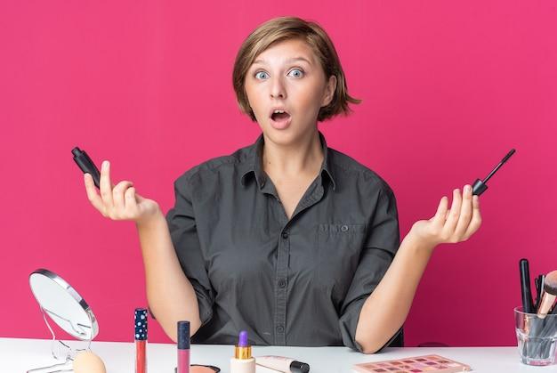 Überraschte junge schöne frau sitzt am tisch mit make-up-tools und hält wimperntusche, die hände ausbreitet